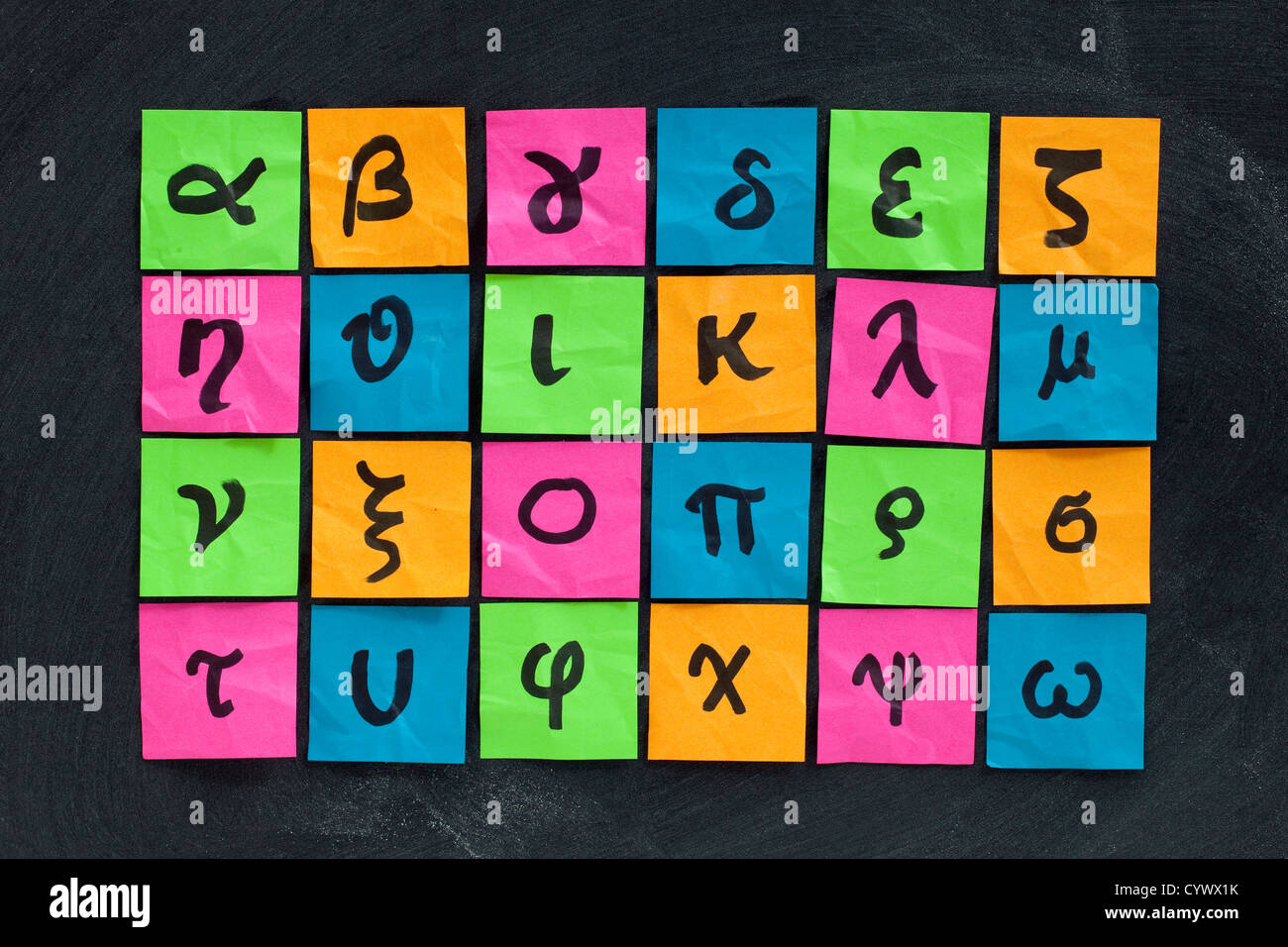 Greek alphabet (lower case) - handwriting on colorful sticky notes posted on blackboard with white chalk texture - Stock Image