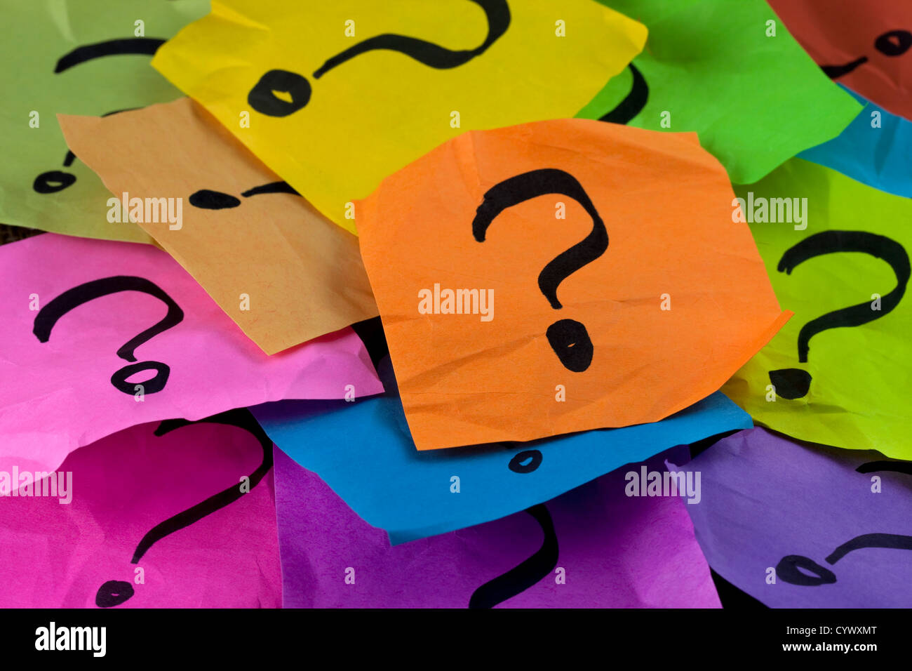 questions, decision making or uncertainty concept - a pile of colorful crumpled sticky notes with question marks - Stock Image