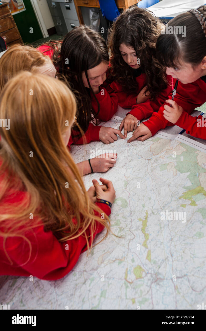 A group of teenage girls looking at an Ordnance Survey map in a geography lesson secondary school wales uk - Stock Image