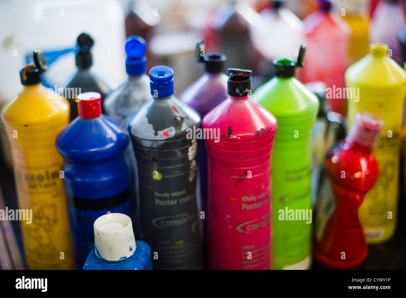 Bottles of acrylic paints in an art class lesson in a secondary comprehensive school in Wales UK - Stock Image