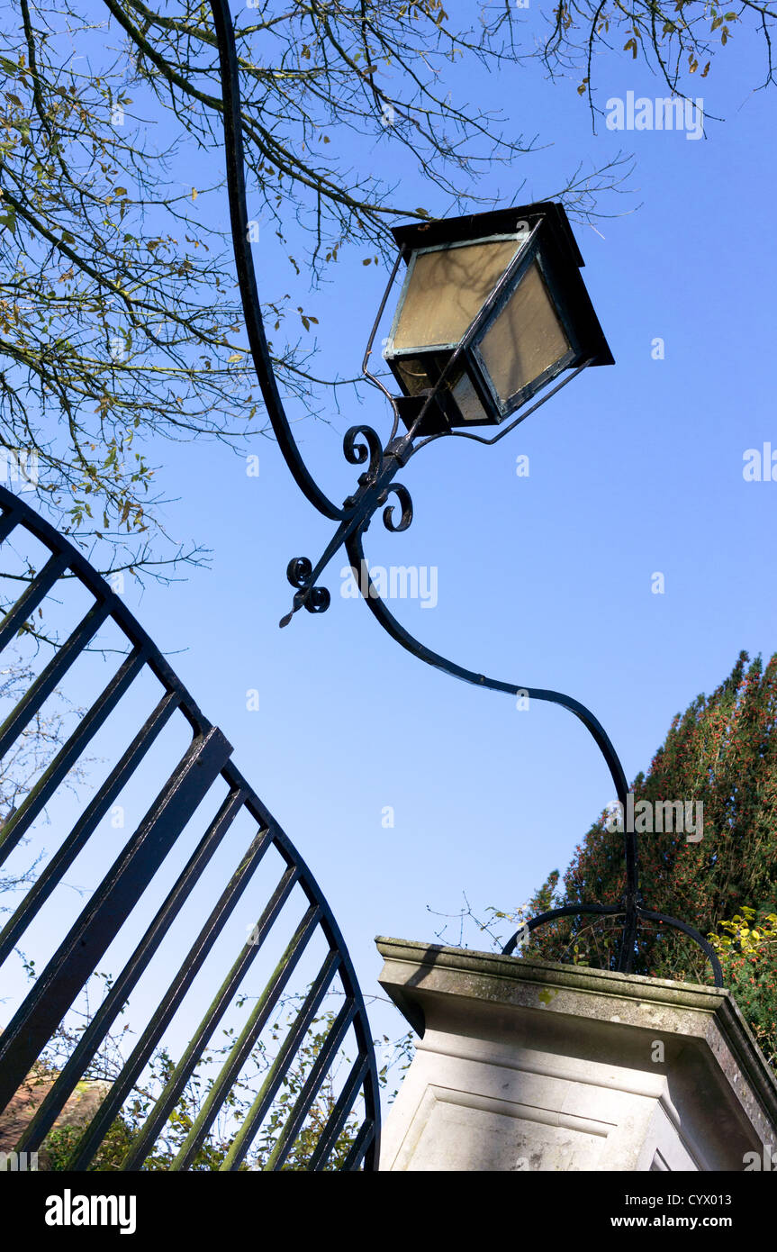 Looking up at old coach lamp over wrought iron gate against blue sky - Stock Image