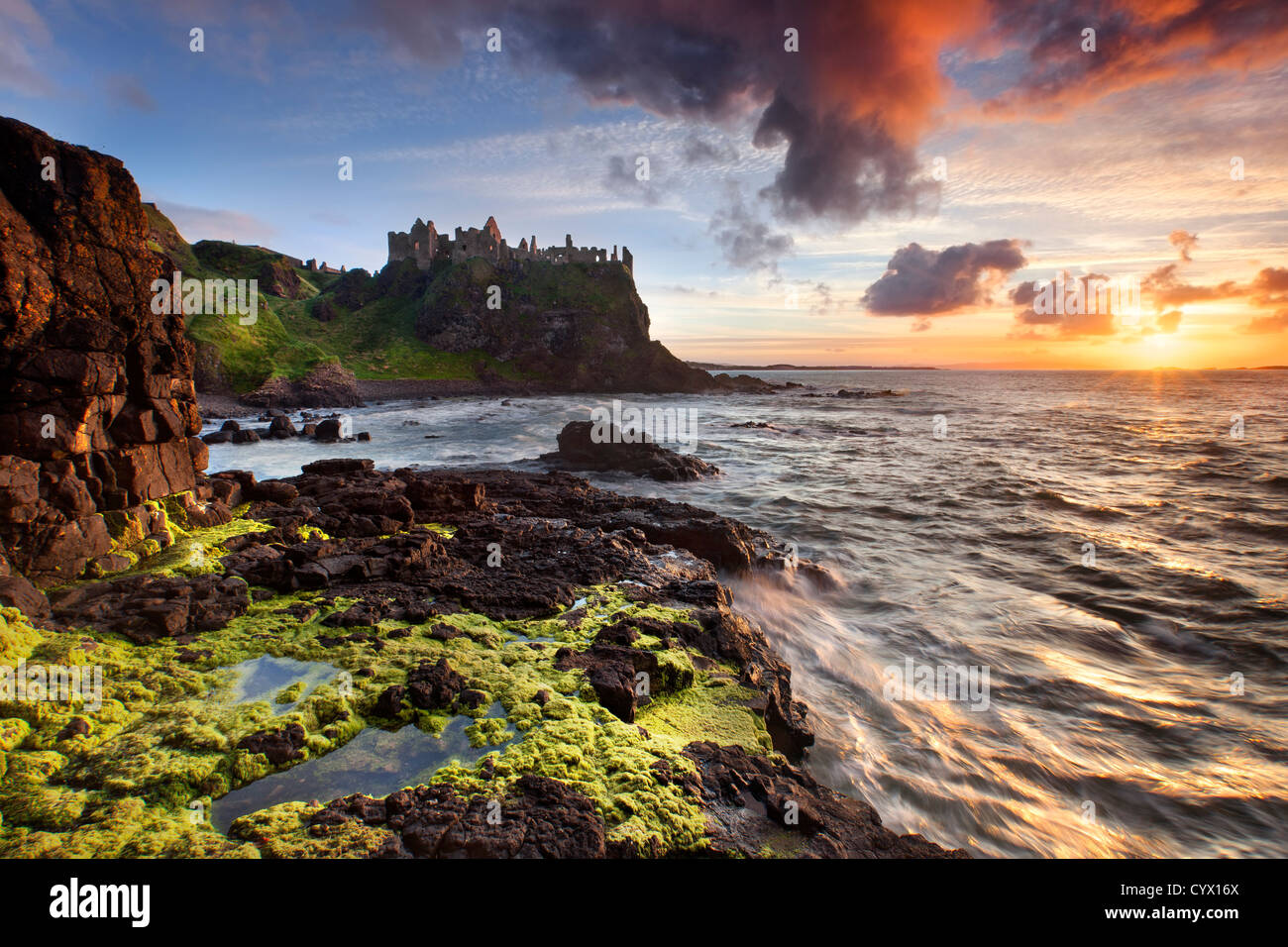 Duluce castle at sunset on the Antrim coast, Northern Ireland. Stock Photo