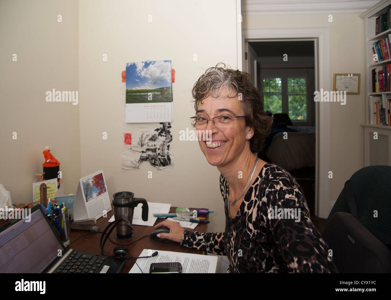 Woman sitting at her desk in home office working, looking at camera smiling - Stock Image