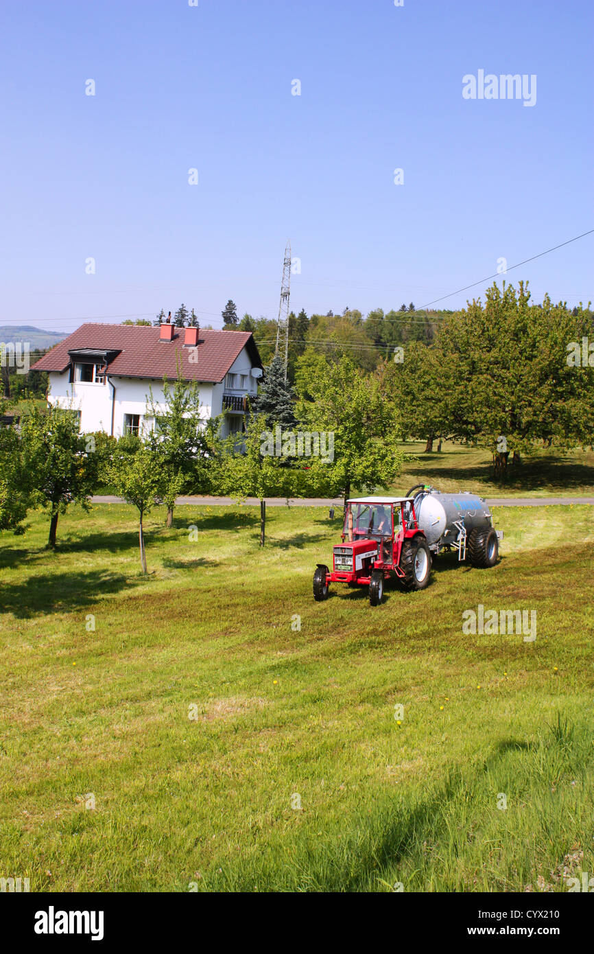 Red tractor in green field in Switzerland Stock Photo