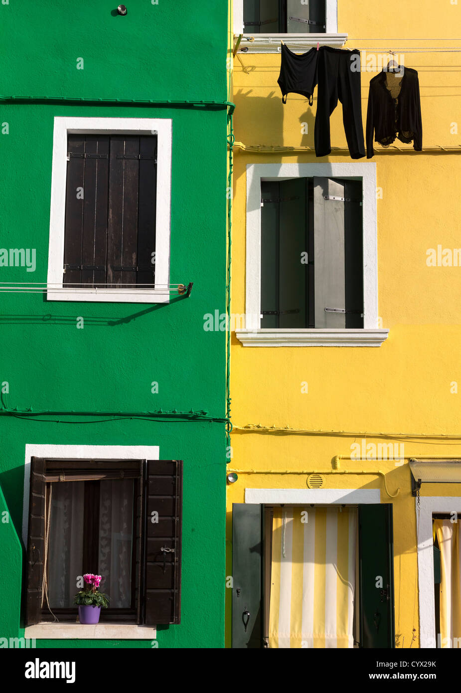 Burano houses painted in typically bright and contrasting colours, in this case pea-green and lemon-yellow - Stock Image