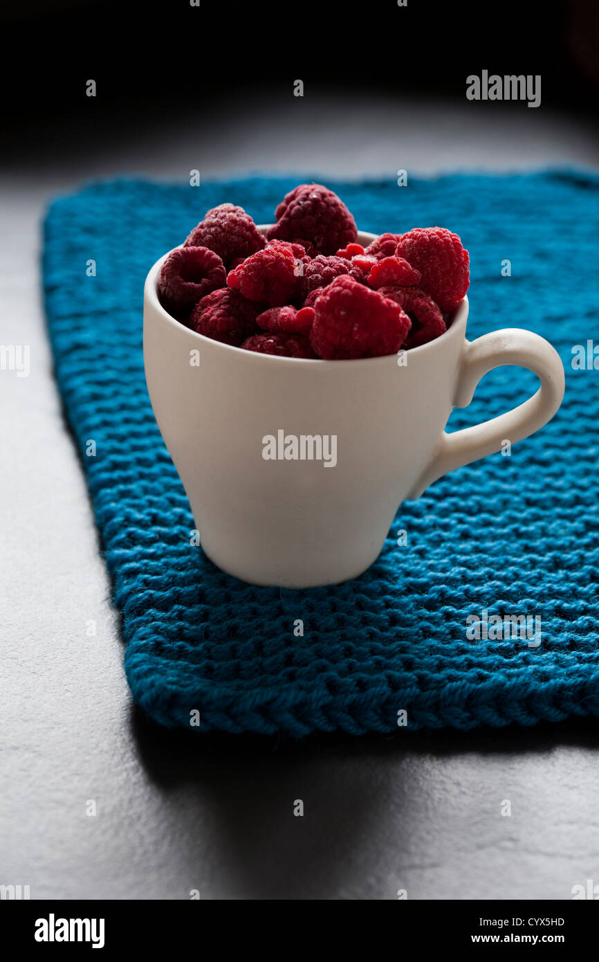 Closeup of fresh raspberries in white cup on a blue mat with shaddow background - Stock Image