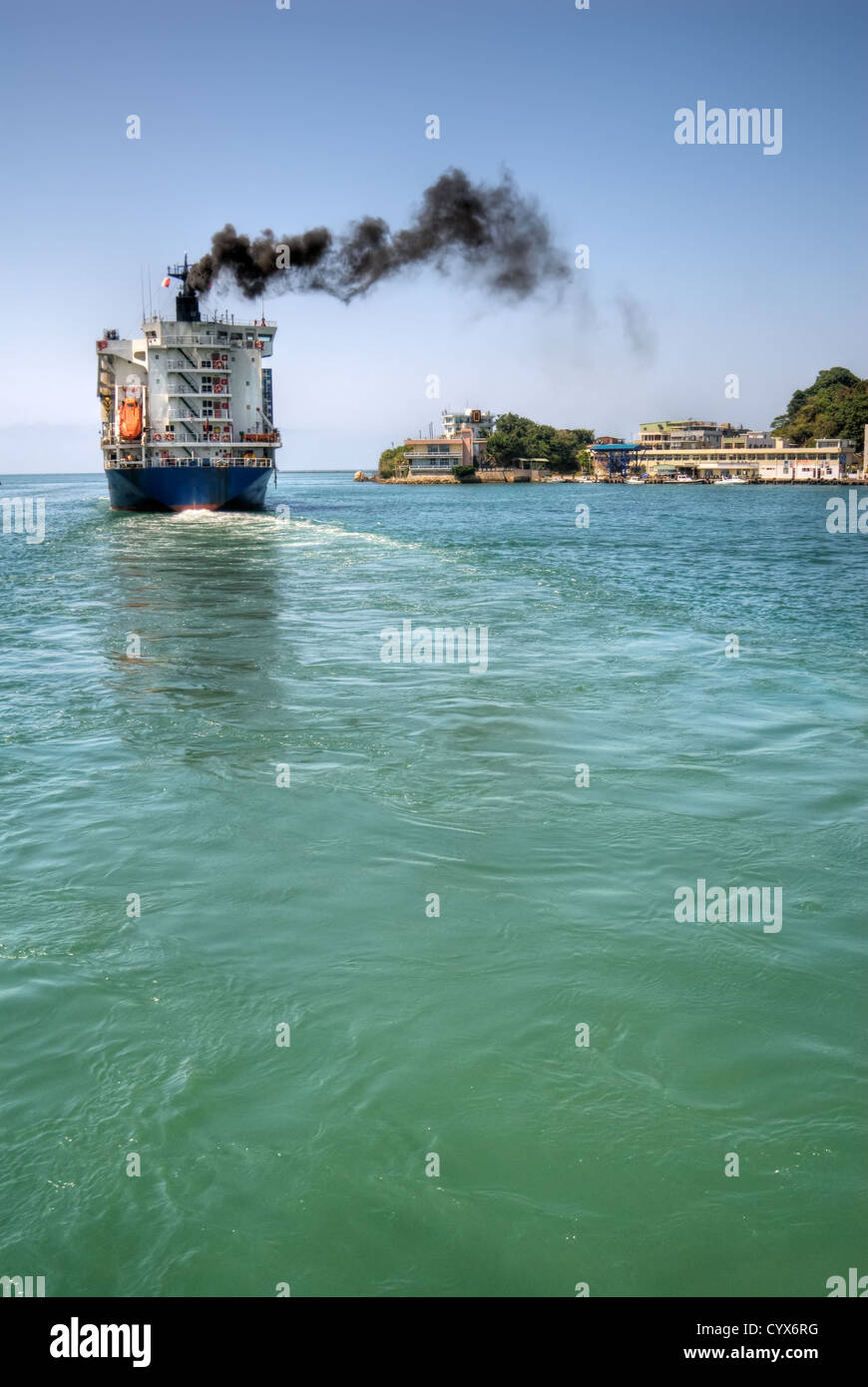 Freighter navigate the port with black smoke of sea in Kaohsiung, Taiwan. - Stock Image
