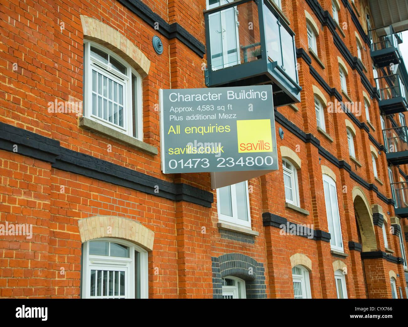 Savills estate agent sign converted industrial waterside character building Ipswich wet dock, Suffolk, England - Stock Image