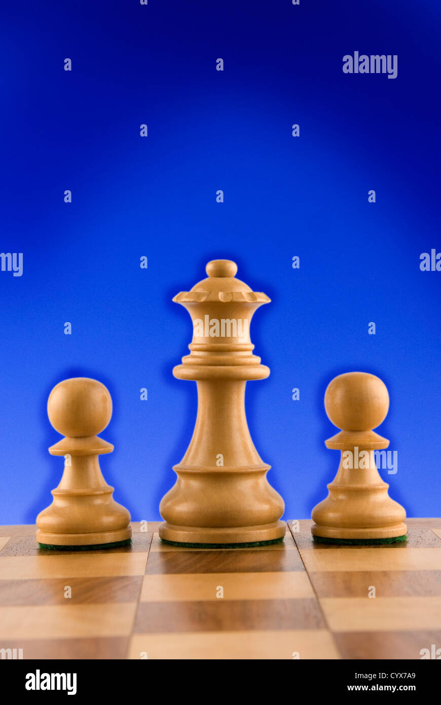 Close-up of chess queen and pawns - Stock Image