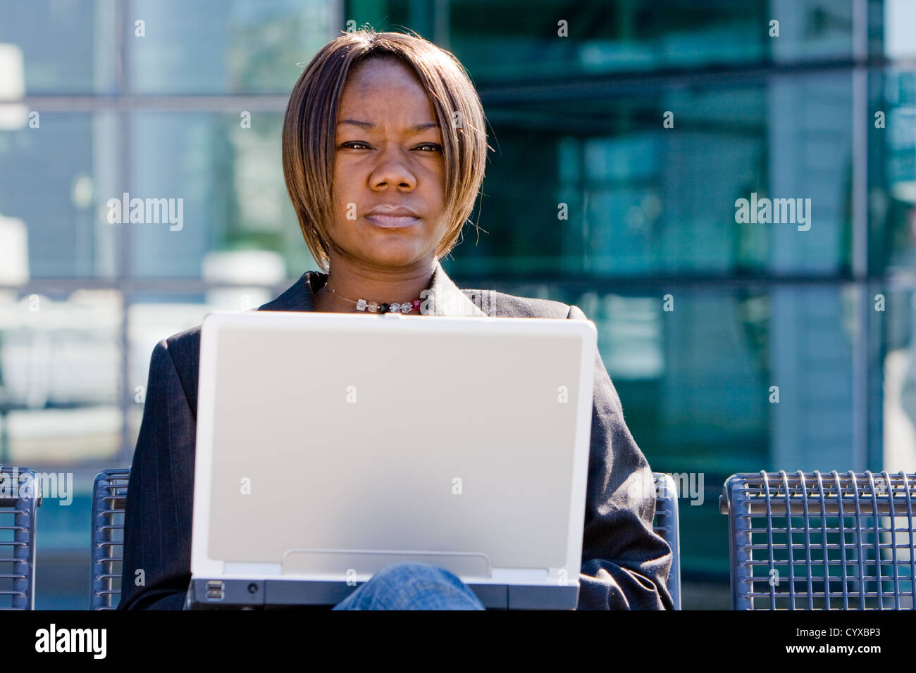 African american business woman with a computer notebook browsing outside an office building Stock Photo