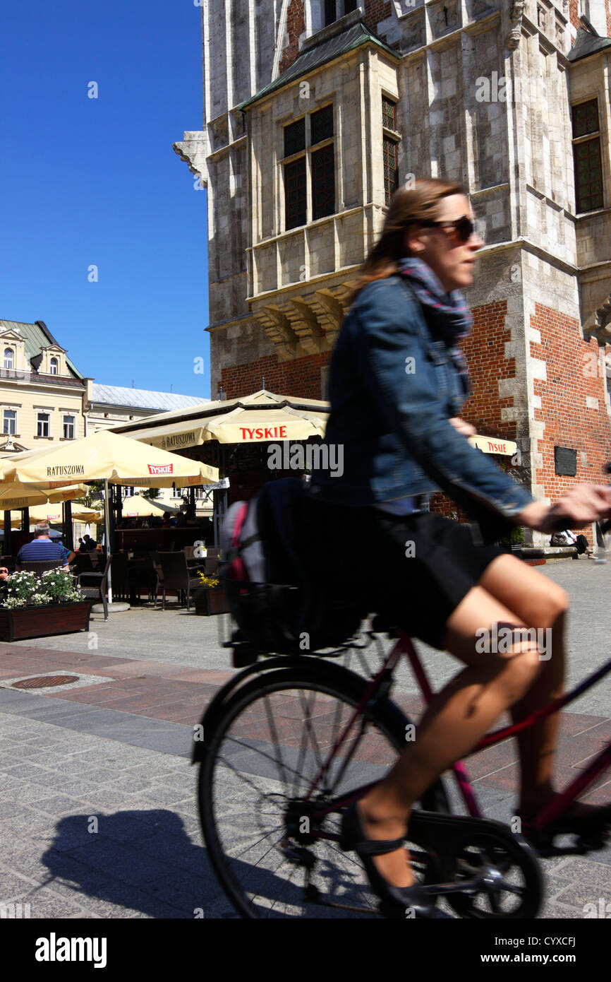 Woman with miniskirt and sunglasses cycling past old town hall tower in main market square. Krakow, Poland - Stock Image