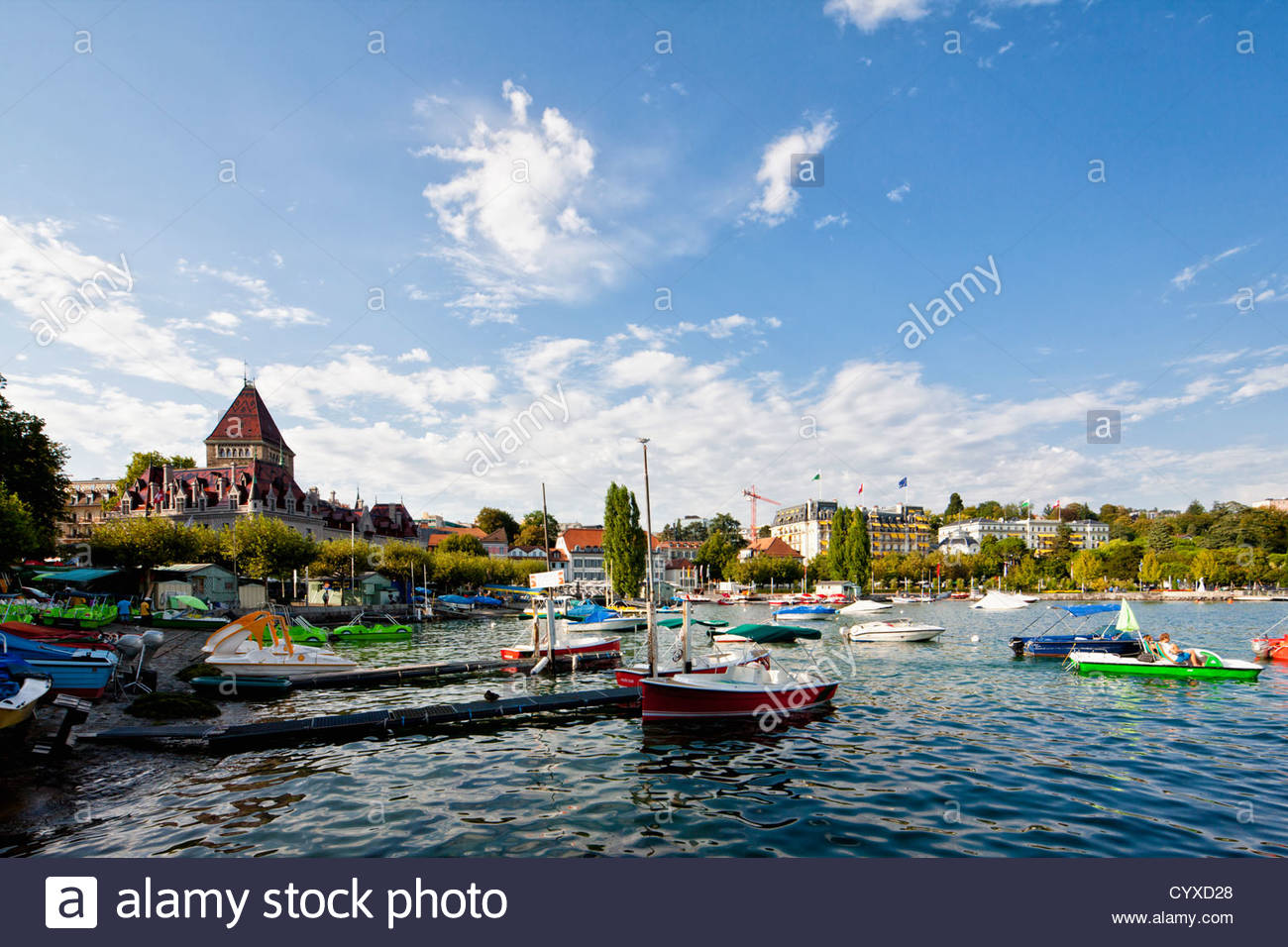 Switzerland, Lausanne, View of sailing ships and paddleboat in port - Stock Image