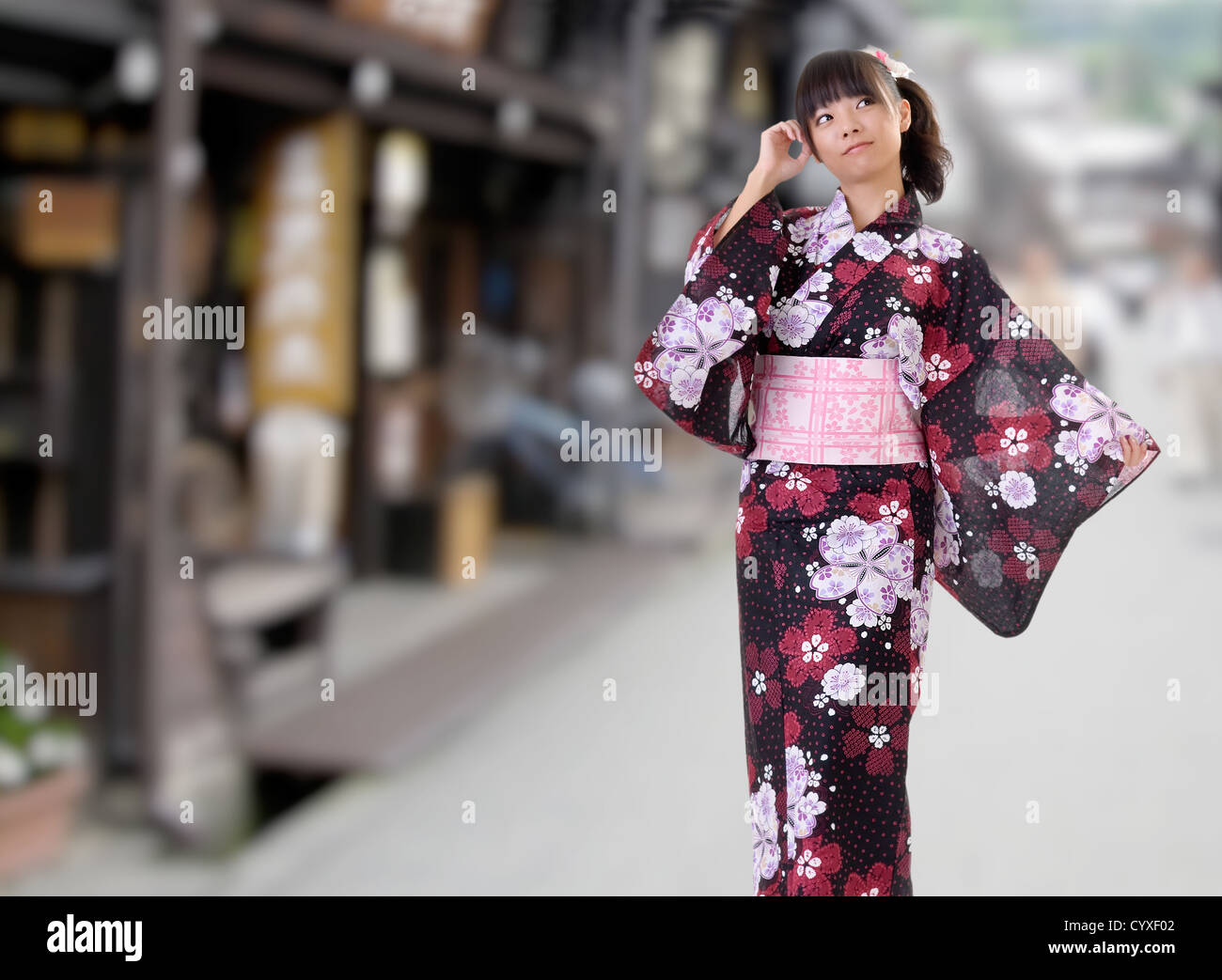 Japanese girl walking on street with blurred background. - Stock Image