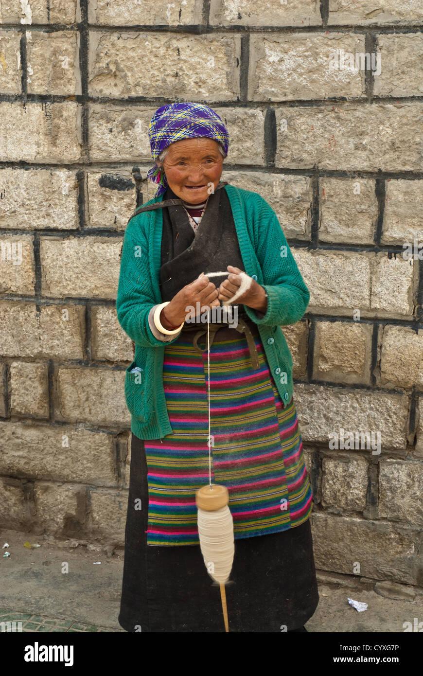 Old Tibetan woman spinning wool, Tibet, China - Stock Image