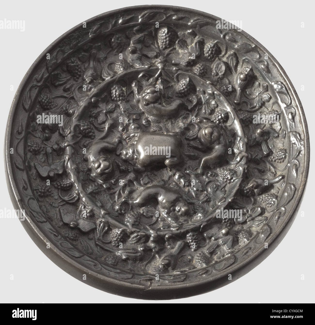 A Chinese hand mirror, Tang dynasty 7. / 8. century Bronze with fine age patina. Finely polished even mirrorside. - Stock Image