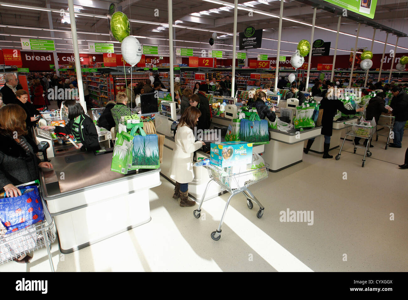 Busy check outs with queueing customers British Isles Great Britain Northern Europe Shop Shops Shoppers Mall Retail - Stock Image