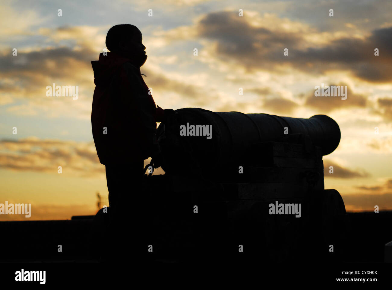 silhouette of a boy at sunset with a cannon - Stock Image