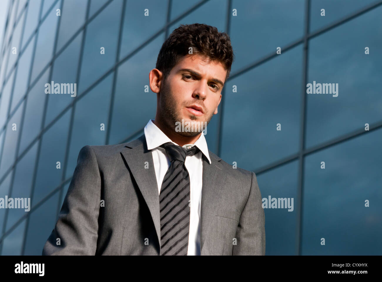 Young businessman looking to camera on modern building background Stock Photo