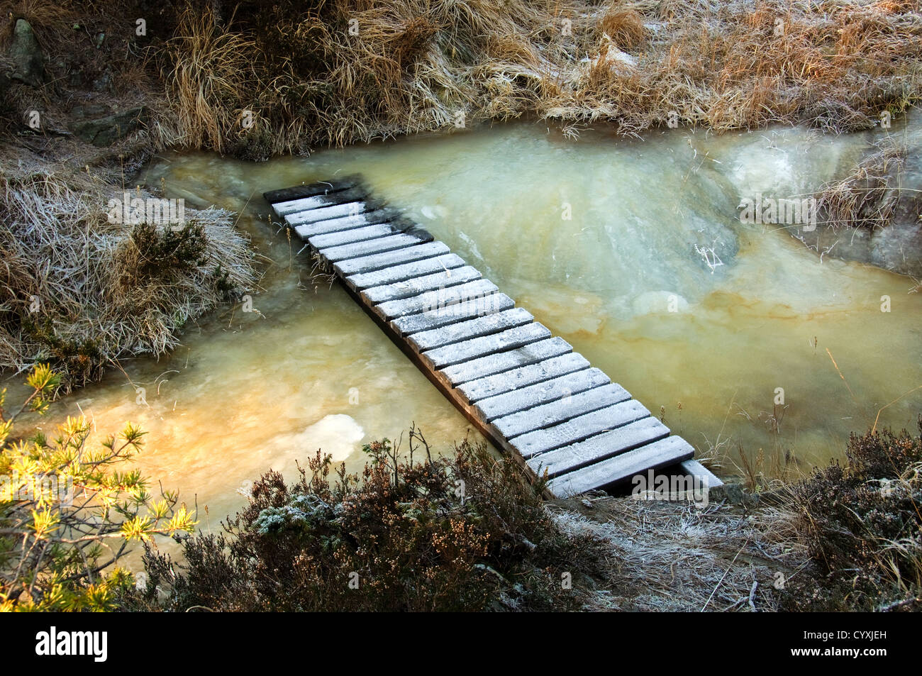 A wooden bridge over an icy stream - Stock Image