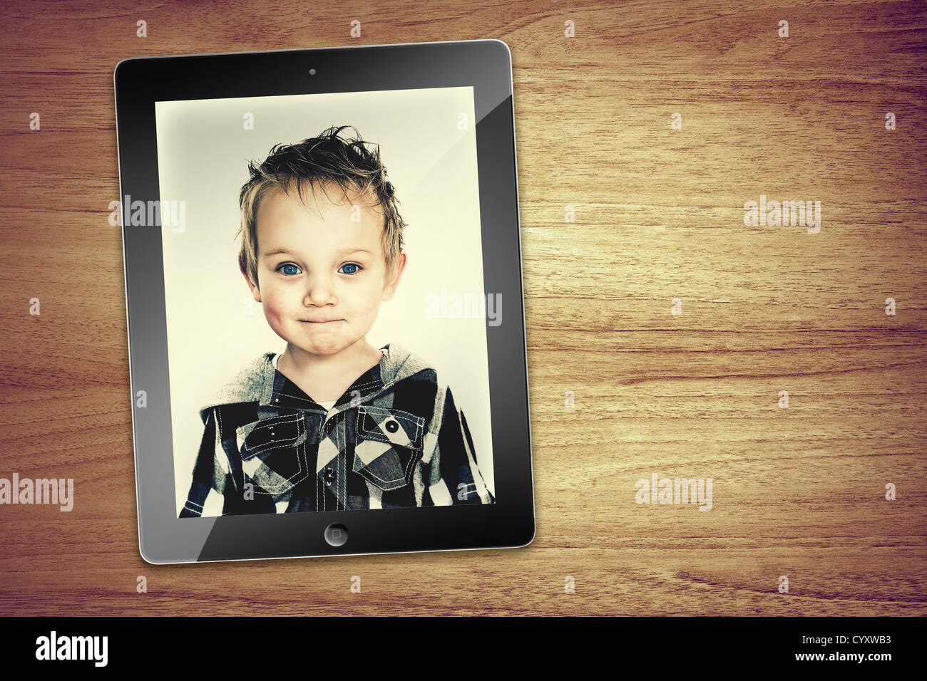 portrait of young boy on tablet - Stock Image
