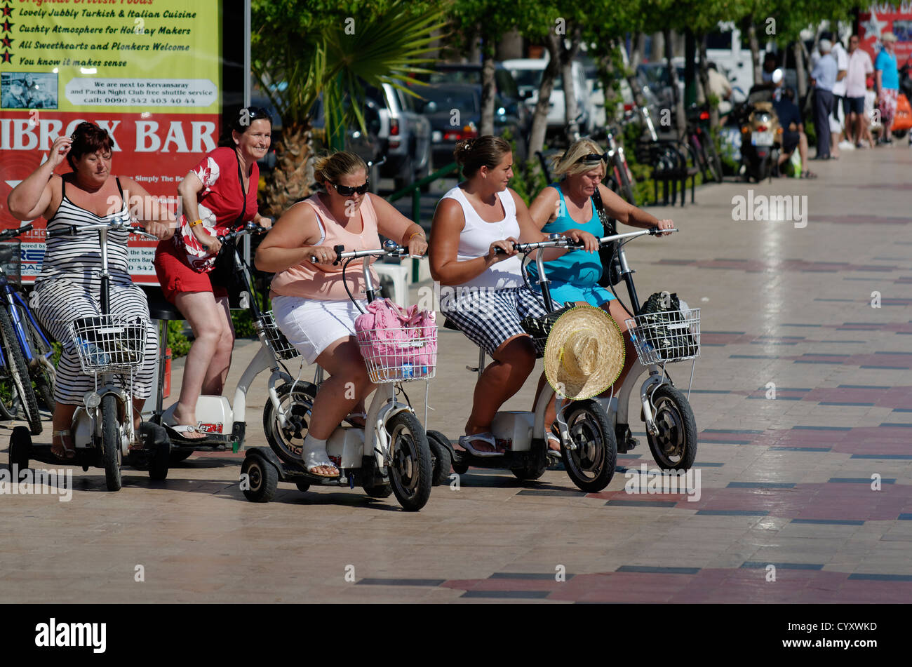 Tourists on rented tricycle scooters at Marmaris Seafront promenade. - Stock Image