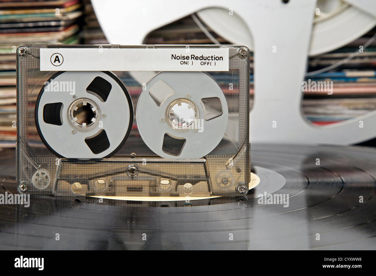 Compact-cassette being on a vinyl record and audio analog tape and vinyl record covers in the distance - Stock Image