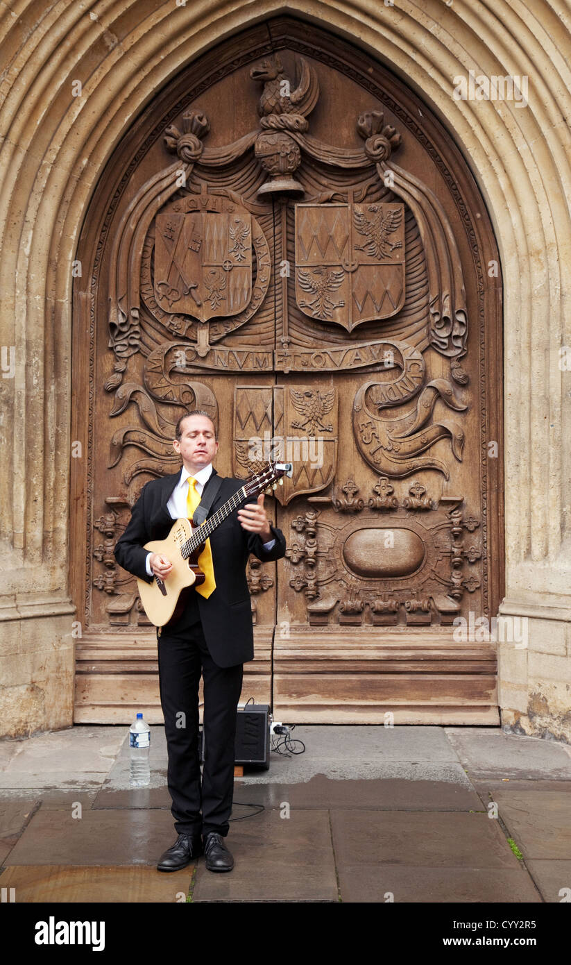 A street musician busker playing guitar at the Abbey door, Bath Somerset UK - Stock Image