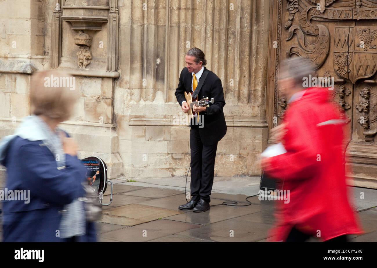 A street musician busker playing his guitar outside the Abbey, Bath Somerset UK - Stock Image
