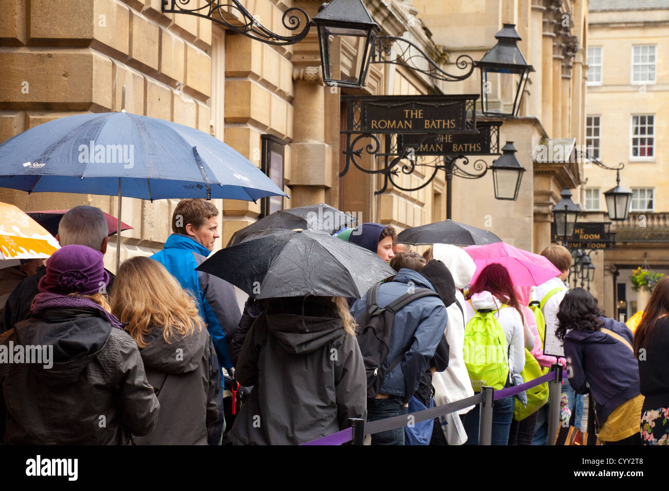 Crowds of people in a queue in the rain to get into the Roman Baths, Bath Somerset UK - Stock Image