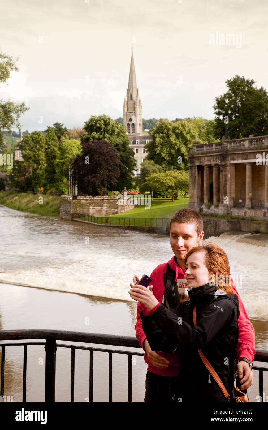 A young couple taking their photo ( taking a selfie ), by the river Avon at Bath Somerset UK - Stock Image