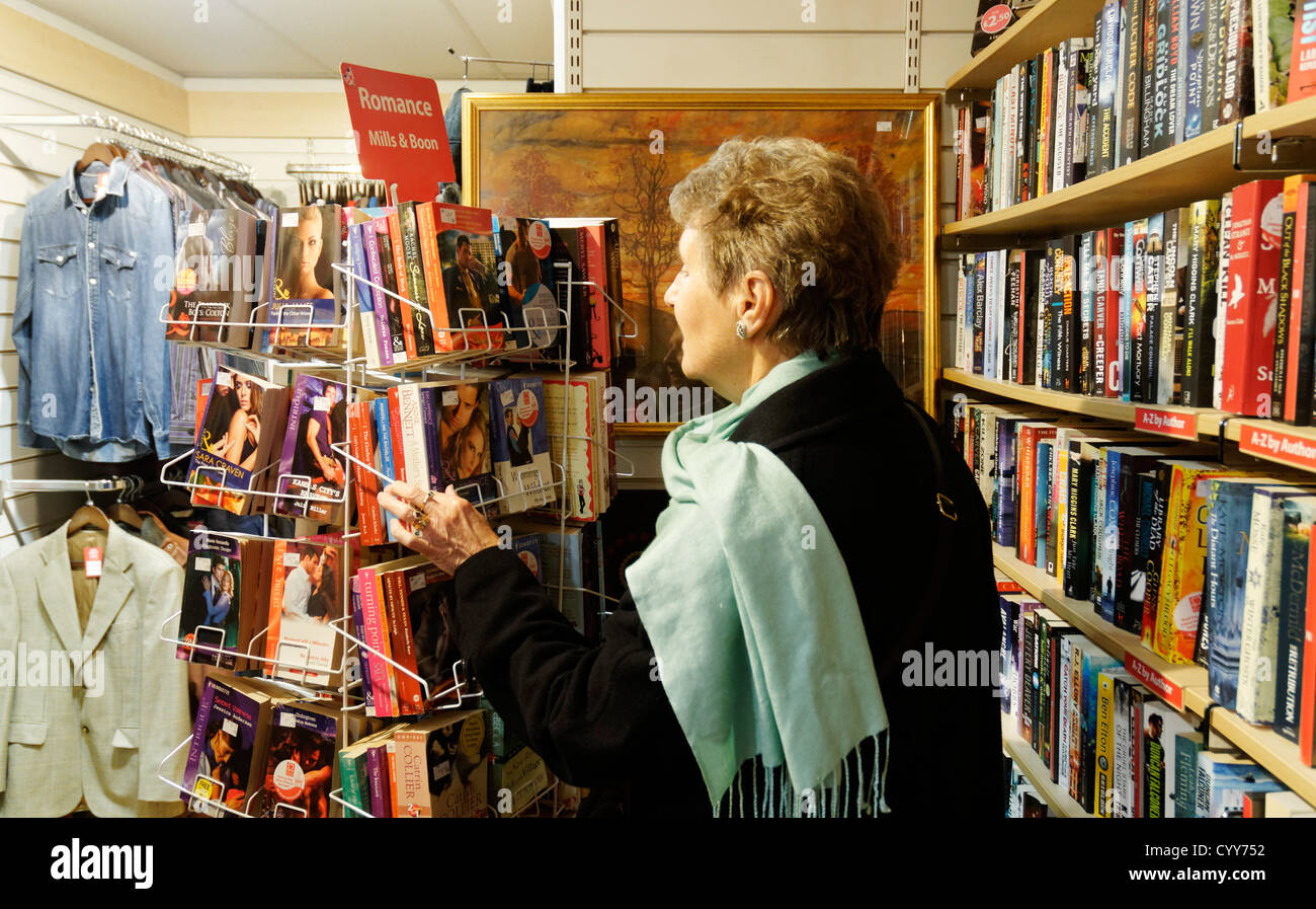 An older lady looking at Mills and Boon books in a charity shop in England - Stock Image