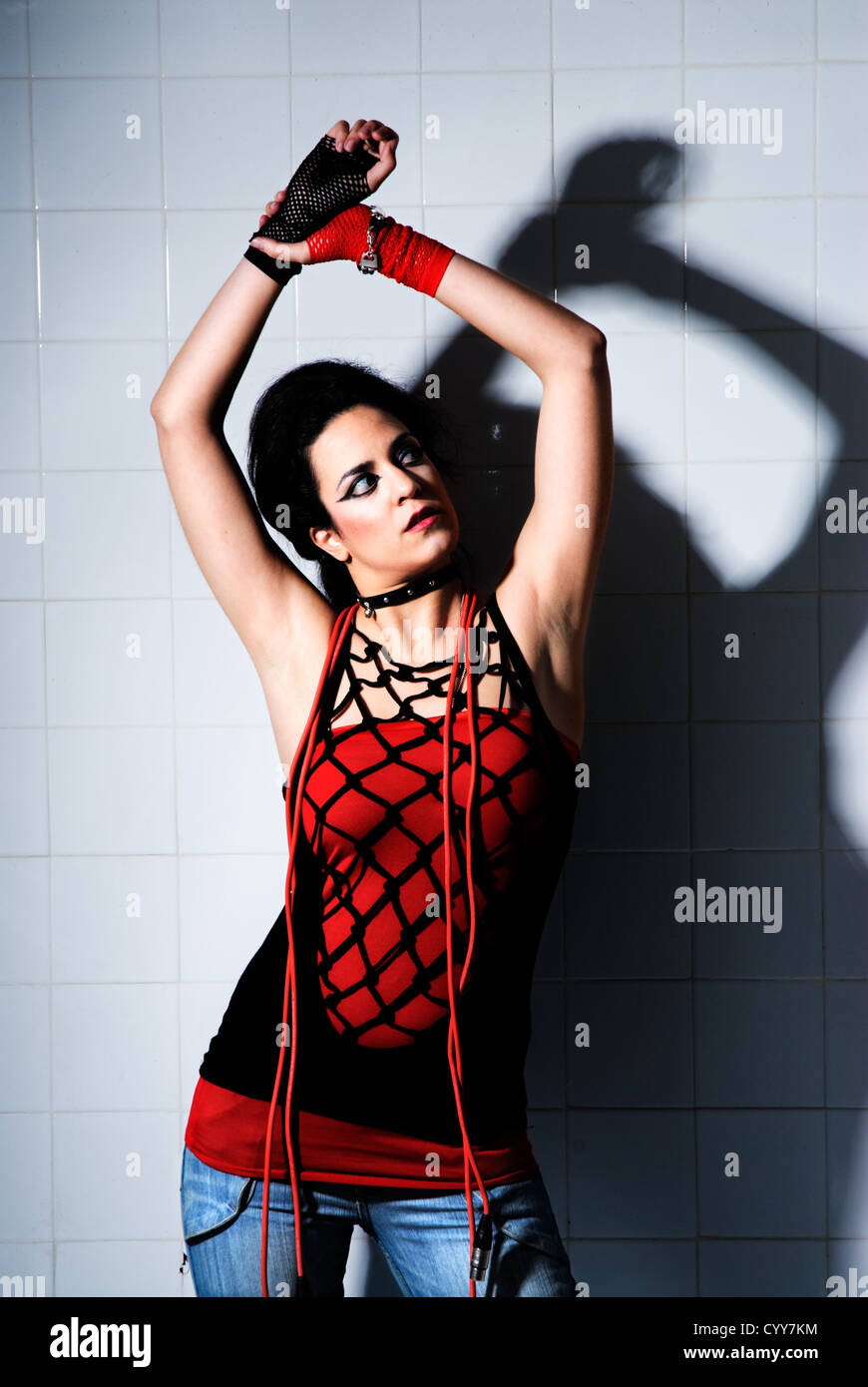 Punk Girl posing hard on an 'underground' background high contrast - Stock Image