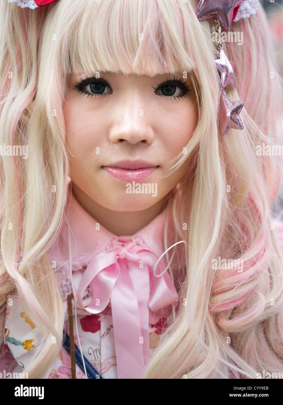 Young Japanese woman in kawaii lolita alternative fashion costume with blonde hair and pink dress - Stock Image