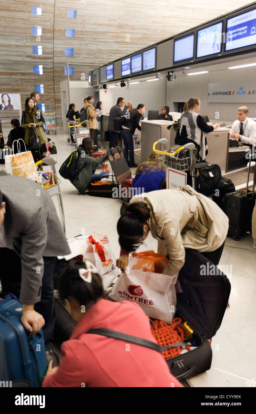 Passengers organizing their  luggage to avoid overweight charges at Charles DE Gaul check in airport Paris - Stock Image