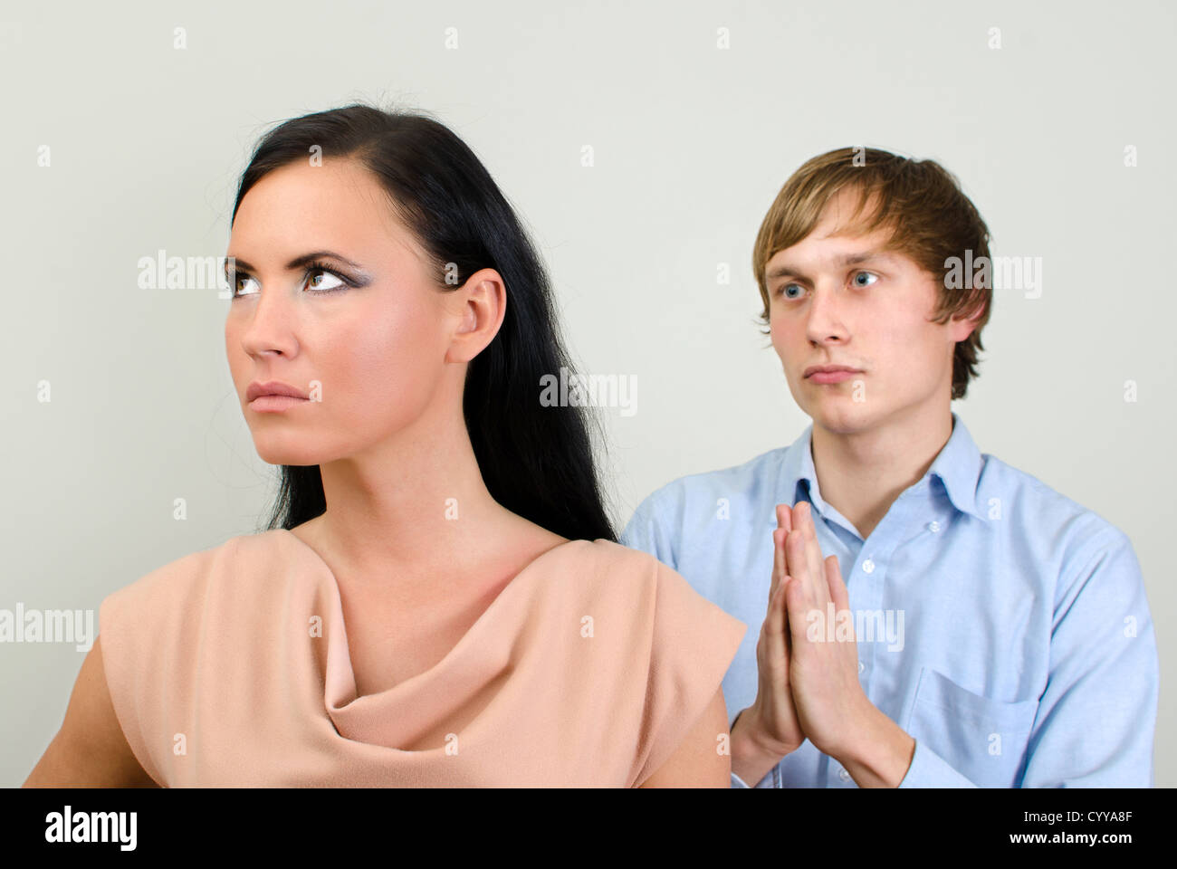 Young couple quarreling. Man asks for forgiveness. - Stock Image