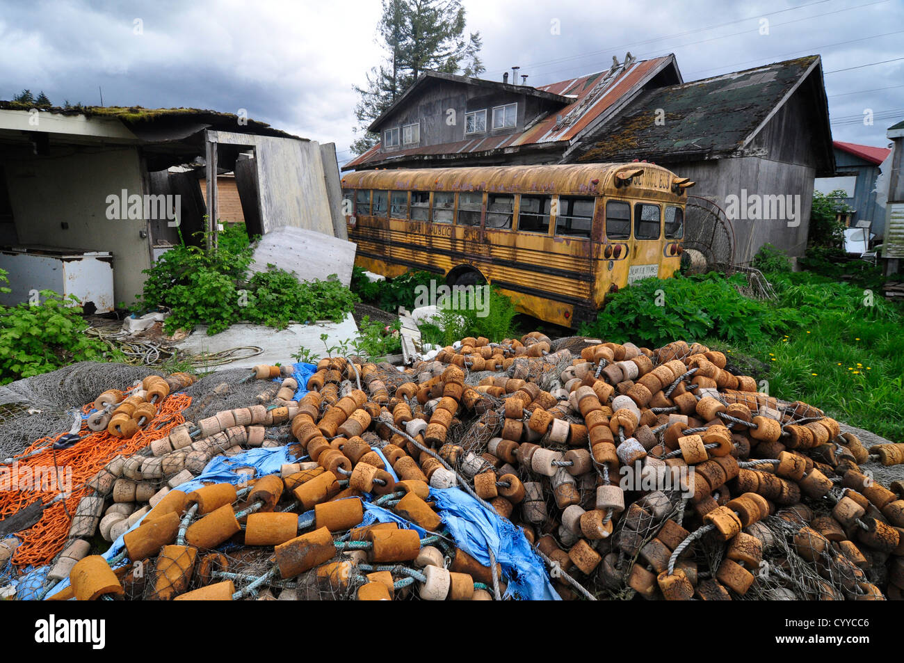 Fishing net and school bus in the backyard of a house in the Tlingit native community of Kake, Alaska. - Stock Image
