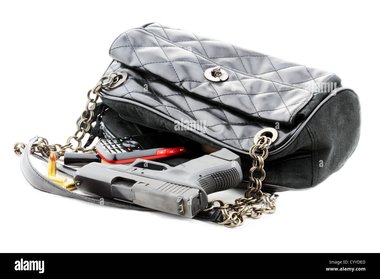 Carried concealed. Handgun and accessories falling from a woman's purse. Isolated on white with light shadow. - Stock Image