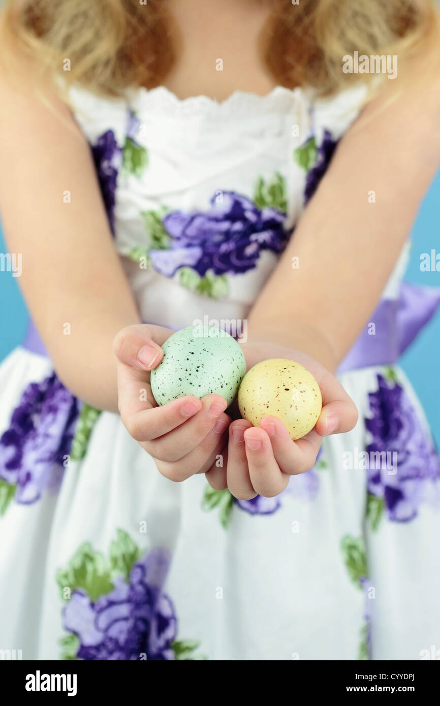 Little girl in her Easter dress holds out two beautifully decorated Easter eggs. - Stock Image