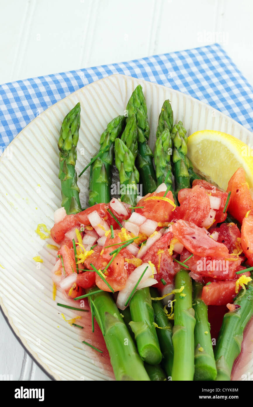 Freshly picked asparagus steamed and served with a tomato and raspberry vinaigrette. - Stock Image