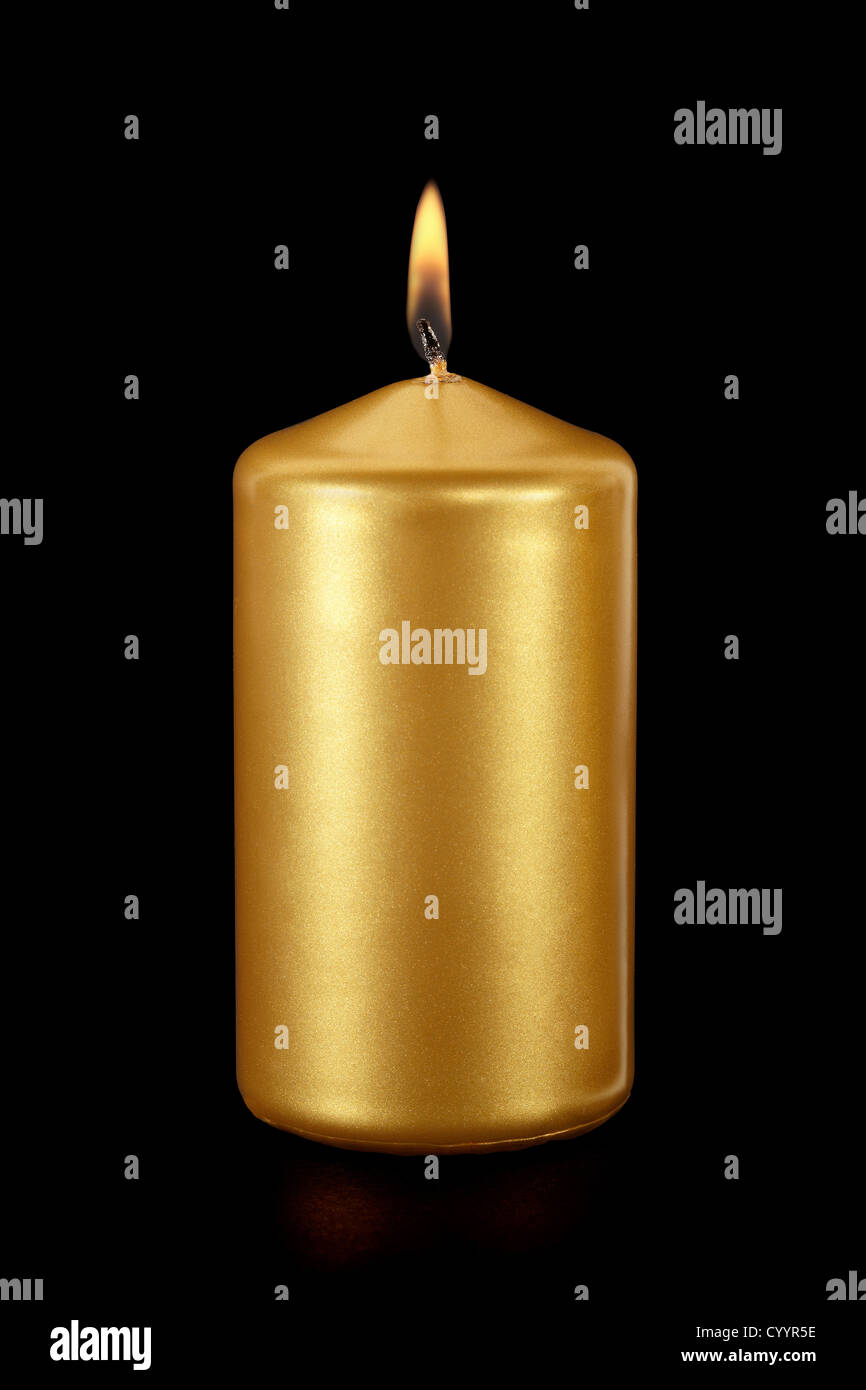 Gold candle on black - Stock Image