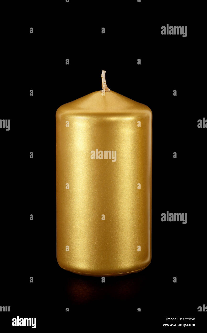 Gold candle on black, clipping path included - Stock Image