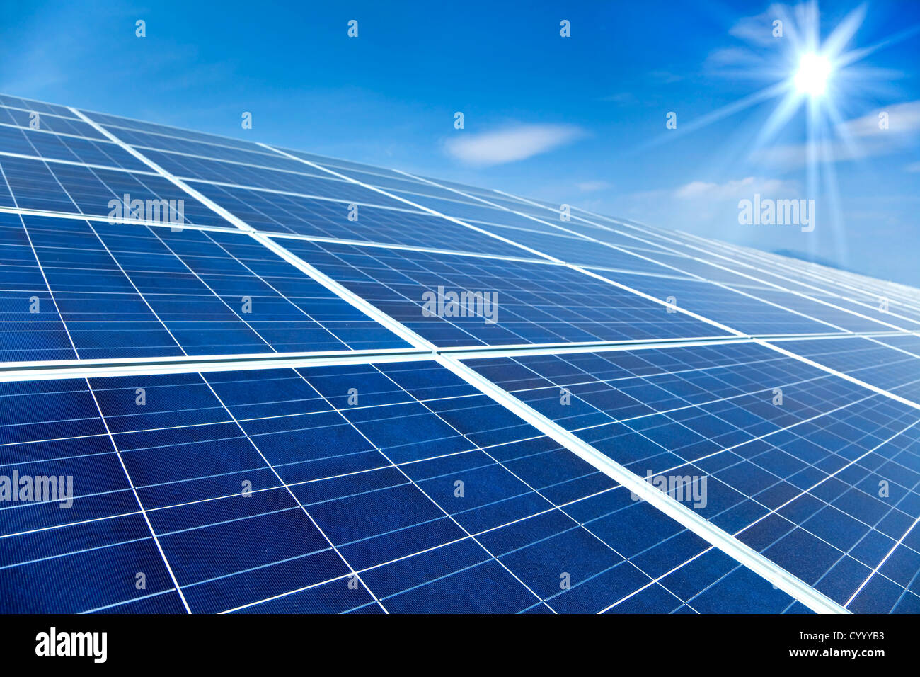 Closeup of Solar Panels with sunlight and blue sky background - Stock Image