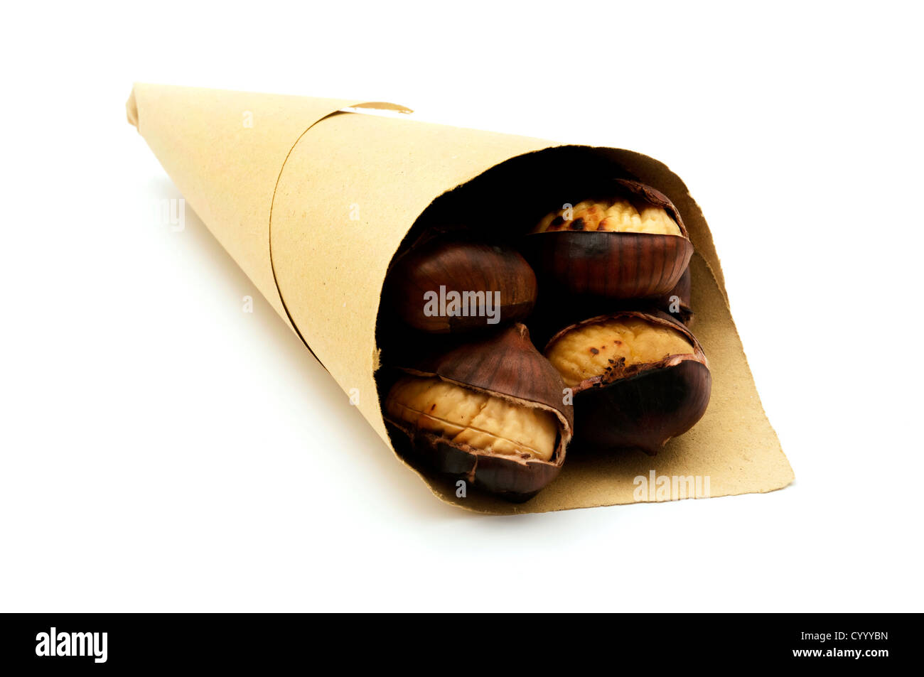 Roasted chestnuts in a paper cone on a white background - Stock Image