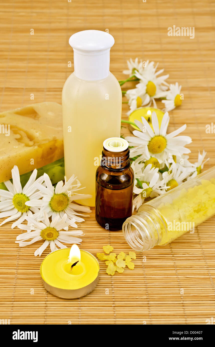 Oil and lotion in a bottle, two homemade soaps, bath salts, two candles with flames and chamomile on a bamboo mat - Stock Image