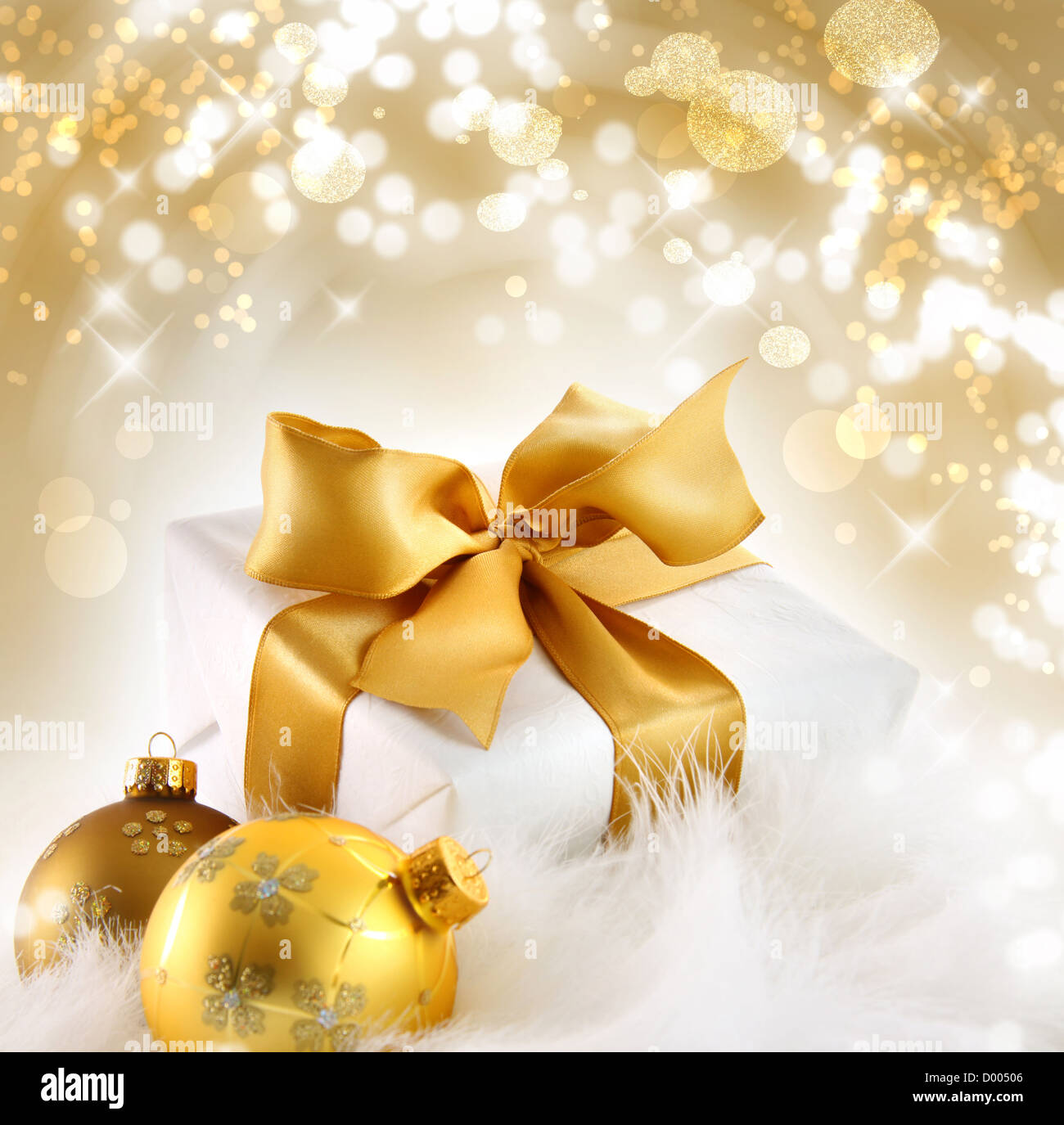 Gold ribboned gift with festive holiday background - Stock Image