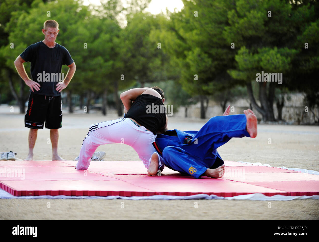 two men wrestle on the ground while a student watches during Martial Arts class outdoors - Stock Image