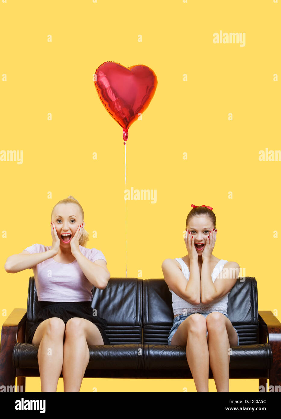 Portrait of two amazed young women sitting on sofa with heart shaped balloon over yellow background - Stock Image
