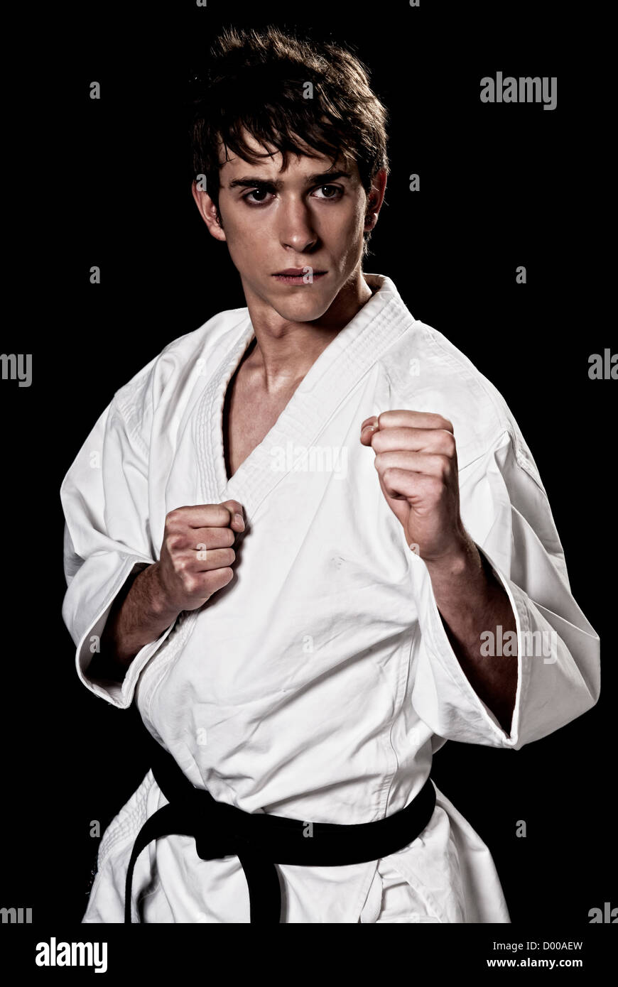 Karate male fighter young high contrast on black background - Stock Image