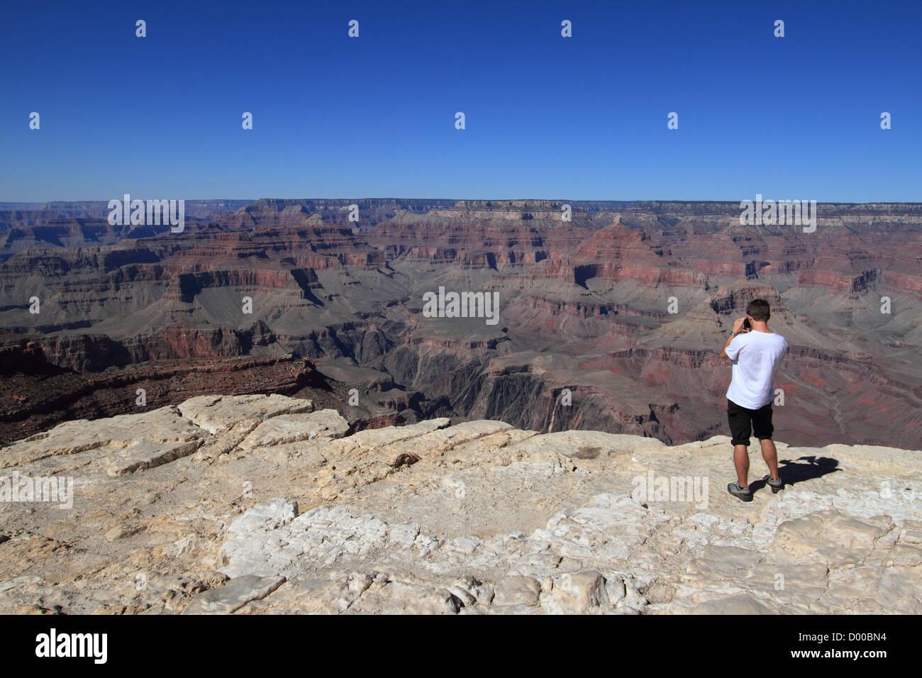 A tourist (not identifiable) photographing Grand Canyon at the South Rim. Grand Canyon, Arizona, USA Stock Photo