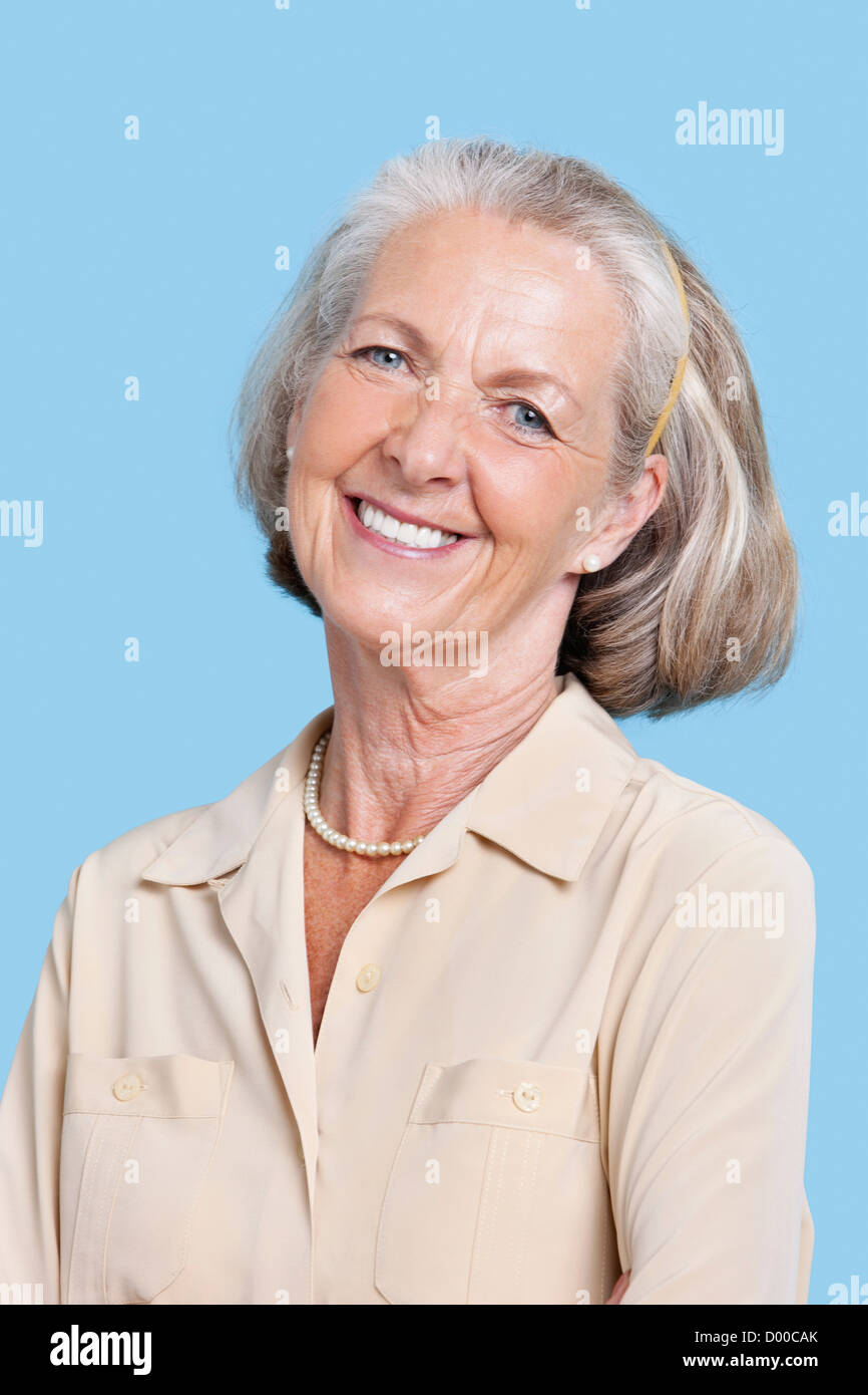 Portrait of smiling senior woman in casuals against blue background - Stock Image